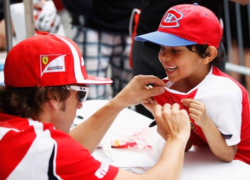 Fernando Alonso firma la camiseta de un niño en Canadá 2011