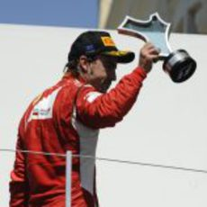 Alonso enseña su trofeo al público español