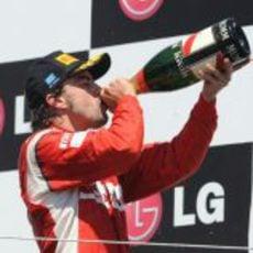 Fernando Alonso bebe de su botella de champán en Valencia