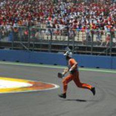 Un comisario recoge el trozo de alerón de Schumacher en Valencia