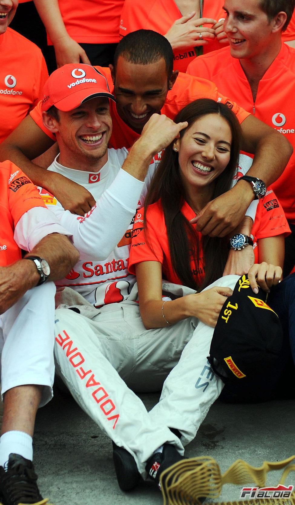 Hamilton abraza a Button y Jessica Michibata en la celebración del equipo en Hungría 2011