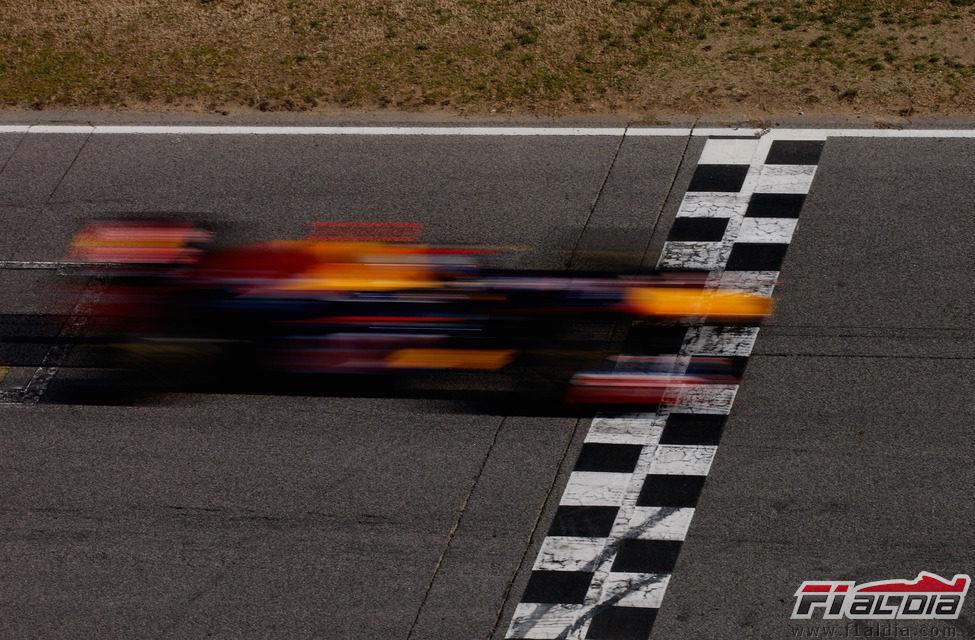Sebastian Vettel pasa a toda velocidad por la línea de meta