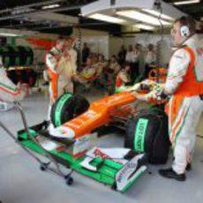 Di Resta sentado en el coche mientras los mecánicos hablan