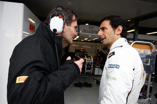 Pedro de la Rosa charla con Luís Pérez-Sala delante del box de HRT