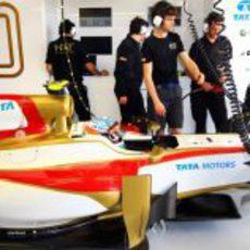 Los mecánicos de HRT siguen trabajando en el coche de Karthikeyan