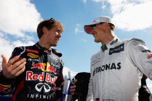 Sebastian Vettel charla con Michael Schumacher antes de la carrera