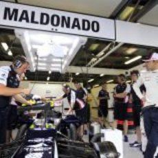 Pastor Maldonado mira como ponen a punto su FW34 durante los primeros libres del GP de Australia 2012