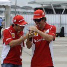 Fernando Alonso enseña algo en su móvil a Felipe Massa