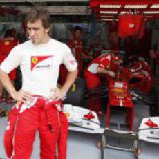 Fernando Alonso con gesto contrariado delante de su box