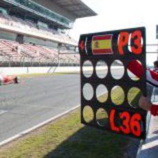 Un mecánico de Ferrari muestra la pizarra a Alonso