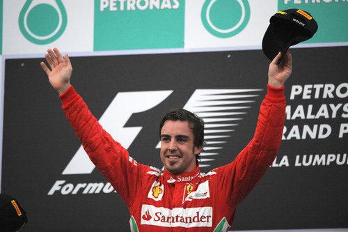 Fernando Alonso levanta los brazos en el podio del GP de Malasia 2012