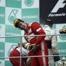 Empapan a Fernando Alonso en el podio de Sepang