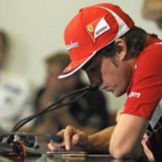 Alonso juega con su iPhone durante la rueda de prensa de la FIA