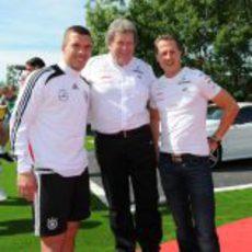 Norbert Haug y Michael Schumacher con Lukas Podolski