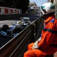 Un comisario de pista observa pasar a Nico Rosberg