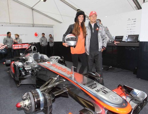 Jenson Button posa junto a su coche y una modelo local