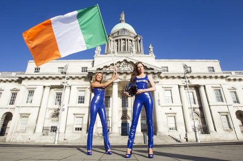 Las azafatas del 'Bavaria City Racing' levantan la bandera de Irlanda