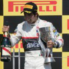 Sergio Pérez sostiene el trofeo y el champán en el podio