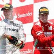 Schumacher y Alonso disfrutan con el champán en el podio de Valencia 2012