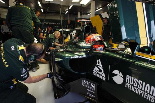 Los mecánicos observan el monoplaza de Heikki Kovalainen