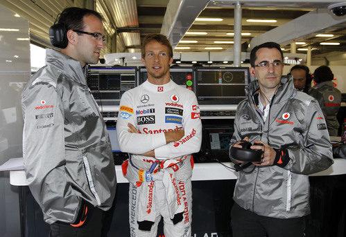 Jenson Button habla con algunos mecánicos del equipo