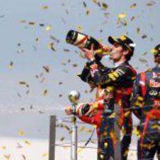 Mark Webber bebe champán en el podio de Silverstone