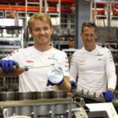 Rosberg lubrica el motor ante la mirada de Schumacher