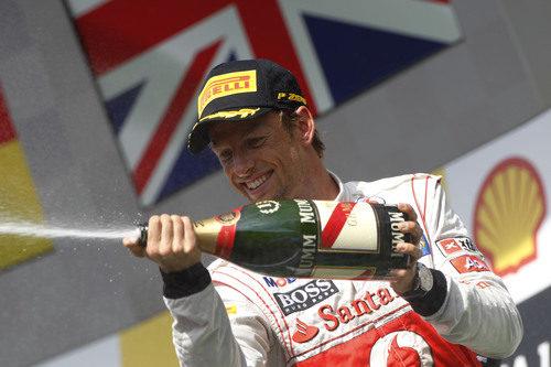 Jenson Button tira champán a su equipo desde el podio