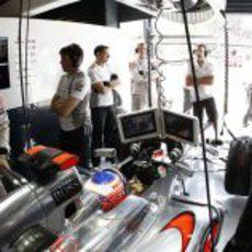 Jenson Button, atento a las pantallas desde el box de McLaren