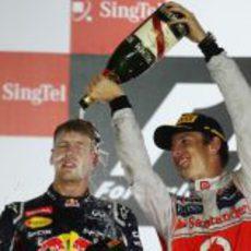 Jenson Button baña en champán a Sebastian Vettel en el podio