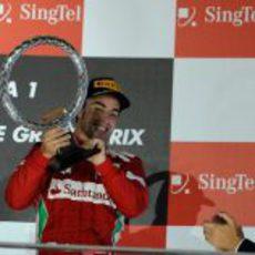Fernando Alonso sostiene el trofeo en el podio