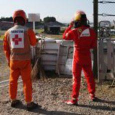 Un comisario y Fernando Alonso mirando la carrera desde las barreras