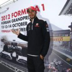 Lewis Hamilton posa ante un cartel promocional del GP de Corea