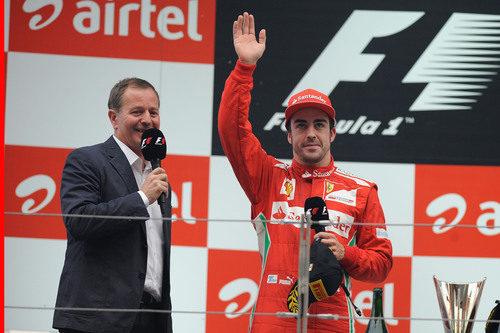 Fernando Alonso saluda desde el podio junto a Martin Brundle