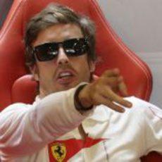 Fernando Alonso señala algo dentro del box de Ferrari