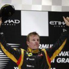 Kimi Räikkönen alza los brazos en el podio de Abu Dabi