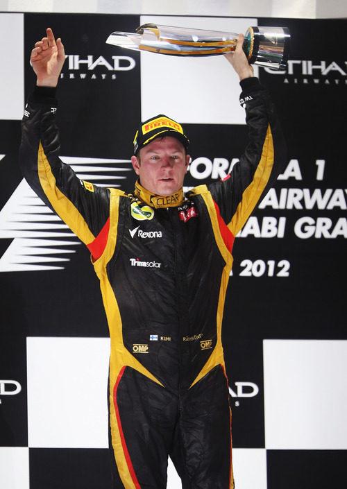 Kimi Räikkönen levanta su trofeo de ganador en el GP de Abu Dabi 2012