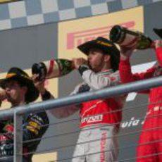 Los tres pilotos beben champán en el podio de Austin