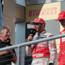 Mario Andretti entrevista a Hamilton y Alonso en el podio