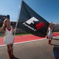 Dos 'pit babes' sujetan la bandera de la Fórmula 1