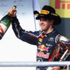 Vettel levanta la botella de champán en el podio de EE.UU.