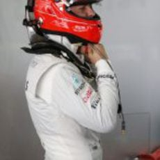 Michael Schumacher se ajusta el casco en el garaje de Mercedes