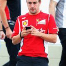 Fernando Alonso con su móvil en Interlagos