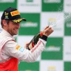 Jenson Button descorcha el champán en Brasil 2012