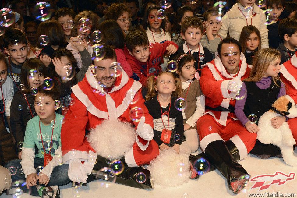 Fernando Alonso y Felipe Massa con los niños