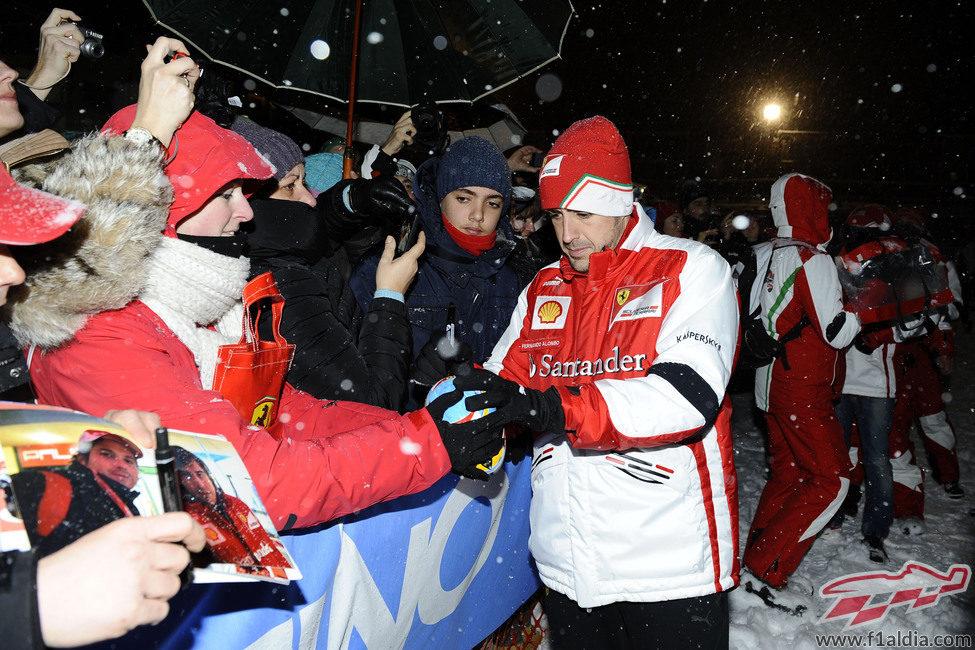Fernando Alonso firma un casco a un aficionado