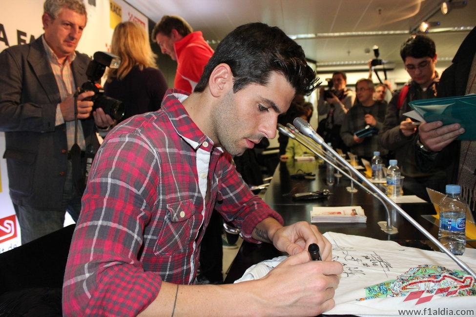 Jaime Alguersuari firmando la camiseta de una aficionada