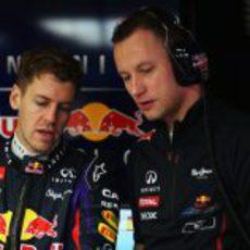 Sebastian Vettel habla con uno de sus mecánicos en el garaje