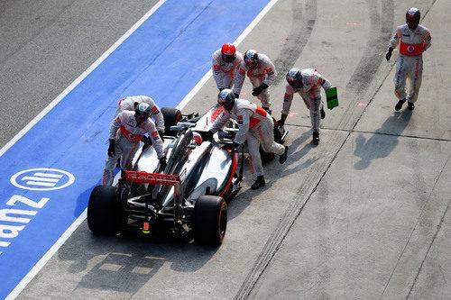 Los mecánicos de McLaren empujan el coche de Jenson Button