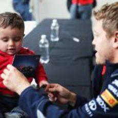 Sebastian Vettel le firma un autógrafo a un niño